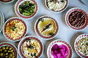A colorful selection of local dishes in a Palestinian restaurant in Abu Dis, just outside the barrier near East Jerusalem, includes hummus, olives, chiles, beets, cabbage slaw, and baba ganoush. (From the book What I Eat: Around the World in 80 Diets.)