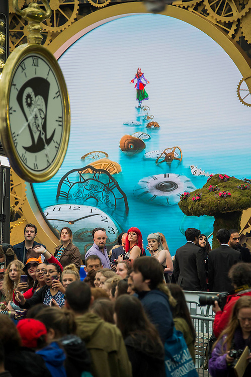 Fans perform in front of a giant screen- Alice Through the Looking Glass premiere - a Walt Disney American fantasy adventure film directed by James Bobin, written by Linda Woolverton and produced by Tim Burton. It is based on Through the Looking-Glass by Lewis Carroll and is the sequel to the 2010 film Alice in Wonderland. The film stars Johnny Depp, Anne Hathaway, Mia Wasikowska, Rhys Ifans, Helena Bonham Carter, and Sacha Baron Cohen and features the voices of Alan Rickman, Stephen Fry, Michael Sheen, and Timothy Spall.