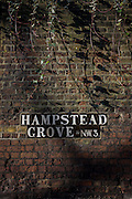 Detail of brick wall with Hampstead Grove NW3 road sign.