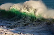 A spectacularly powerful backlit wave breaking off of Oahu, Hawaii