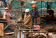 A worker cuts steel rods at a construction site in Shanghai, China on 06 March, 2009.  For the past decade, Shanghai has underwent the largest reconstruction in recorded history, over 20 million square meters of land, approximately a third of Manhattan, were developed between year 200 and 2005 alone.