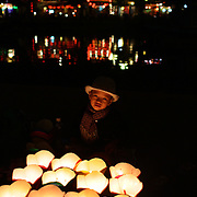 A young vietnamese boy helps his mother sell floating candles to tourist to float down the Thu Bon River, Hoi An, Vietnam. Hoi An is an ancient town and an exceptionally well-preserved example of a South-East Asian trading port dating from the 15th century. Hoi An is now a major tourist attraction because of its history. Hoi An, Vietnam. 5th March 2012. Photo Tim Clayton