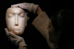 """© Licensed to London News Pictures. 12/11/2018. London, UK. A staff member hangs """"The Man Behind the Mask"""", a Henry Moore'smasterpiece (British, 1898-1986). (Estimate: £1,000,000-1,500,000). The work is one of 12 known, small carvings by Moore titled Mask, and, uniquely, is the only one carved from alabaster.<br /> <br /> Bonhams Modern British and Irish Art photocall. Auction to be held on 14 November 2018. Photo credit: Dinendra Haria/LNP"""