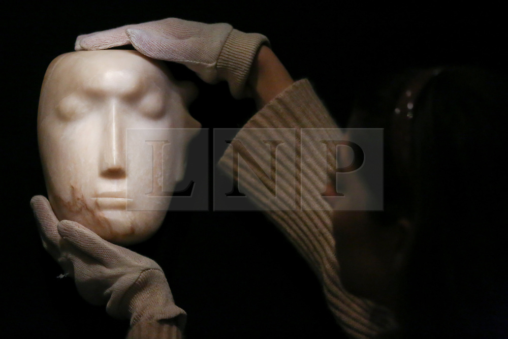 "© Licensed to London News Pictures. 12/11/2018. London, UK. A staff member hangs ""The Man Behind the Mask"", a Henry Moore's masterpiece (British, 1898-1986). (Estimate: £1,000,000-1,500,000). The work is one of 12 known, small carvings by Moore titled Mask, and, uniquely, is the only one carved from alabaster.<br /> <br /> Bonhams Modern British and Irish Art photocall. Auction to be held on 14 November 2018. Photo credit: Dinendra Haria/LNP"