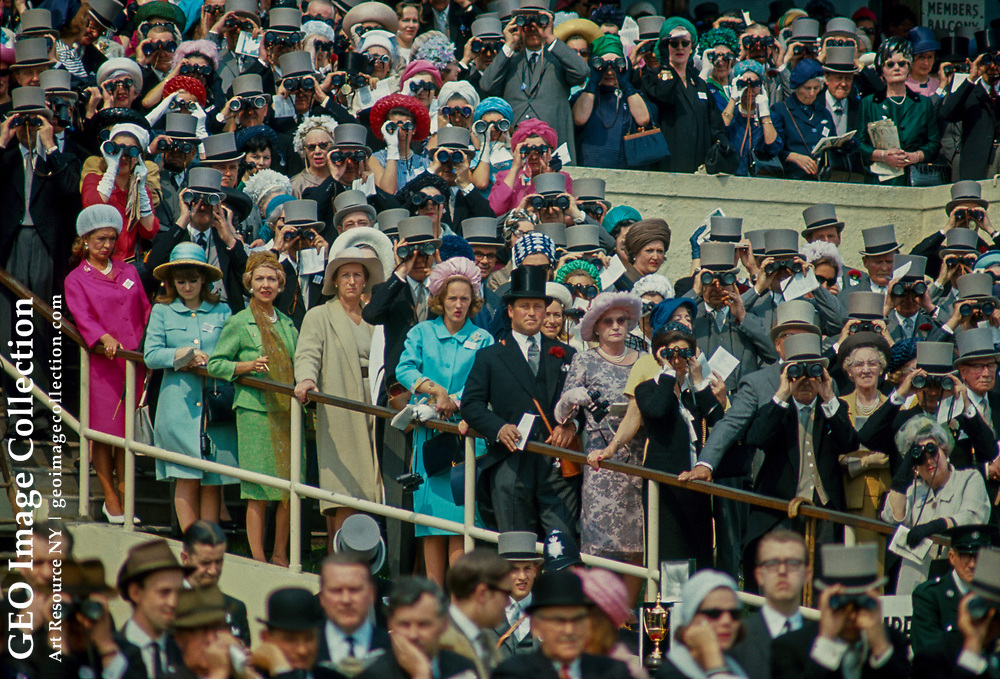 Fashionably dressed crowds watch horse races with binoculars.