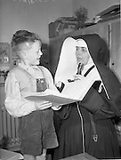 14/05/1959<br /> 05/14/1959<br /> 14 May 1959<br /> School for the Deaf at Mary Immaculate School for the deaf, Beech Park, Stillorgan. With the aid of an amplifier, Sr. Mary Victoria of the Daughters of the Cross Order, helps 6 year old Francis O'Hanlon improve his speech.