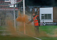 A steward deals with an orange flare thrown from the Blackpool fans during the EFL Sky Bet League 1 match between Fleetwood Town and Blackpool at the Highbury Stadium, Fleetwood, England on 25 November 2017. Photo by Paul Thompson.