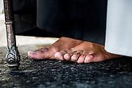 A man, barefoot, waits to restart walking on the black asphalt of a street in Seville. Spain