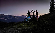 three mountain bikers standing on the peak of a mountain in the alps