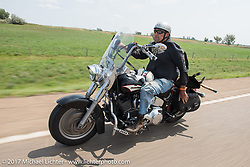 Ed Rieken with his puppy Gypsy in his lap riding north on highway 79 on the Run to the Line for lunch and biker vs Cowboy rodeo games at the Spur Creek Ranch in Newell during the annual Sturgis Black Hills Motorcycle Rally. SD, USA. Wednesday August 9, 2017. Photography ©2017 Michael Lichter.