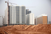 A view of new apartment developments rising from the desert on the outskirts of Yulin, Shaanxi Province, China on 14 August, 2011. Like many coal rich regions in China's arid northwest, a vast amount of mineral wealth has been re-invested into the local economy in the form of speculative real estate ventures, creating hundreds of new cities that claims few real residents.