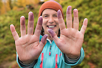Female hiker shows hands stained from picking wild blueberries along Kungsleden trail, Lapland, Sweden