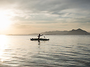 A young boy catching fish on an outrigger canoe. On Maiga island.