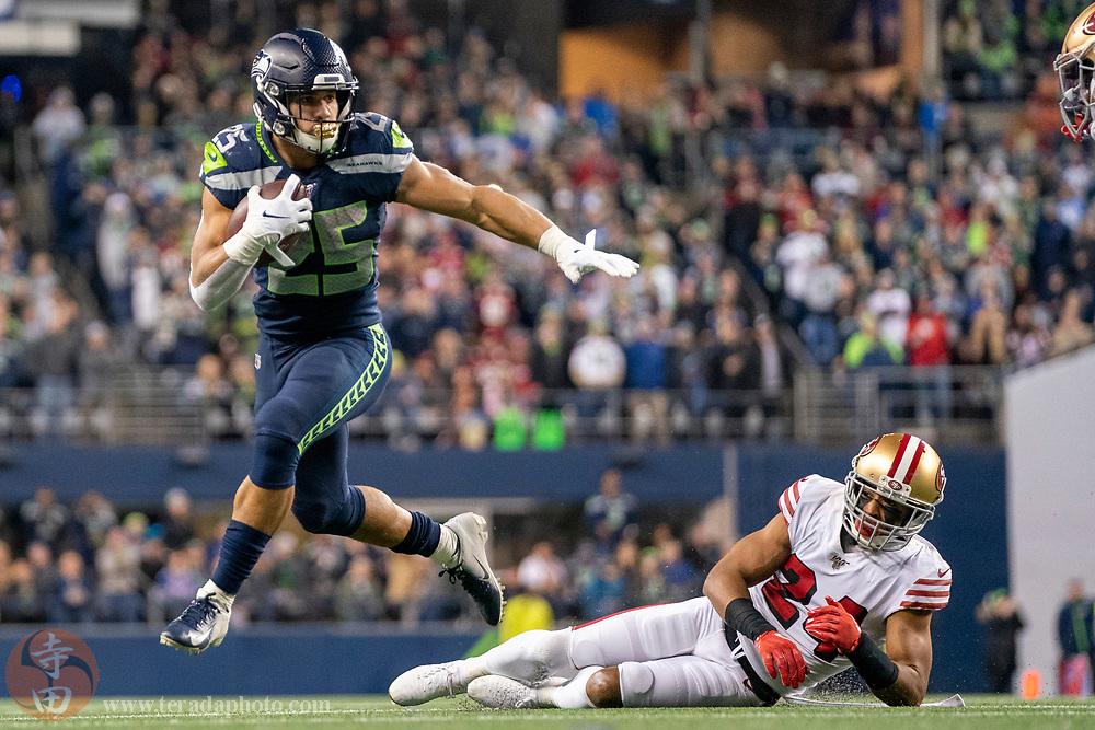 December 29, 2019; Seattle, Washington, USA; Seattle Seahawks running back Travis Homer (25) runs against San Francisco 49ers defensive back K'Waun Williams (24) during the third quarter at CenturyLink Field.
