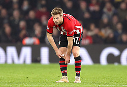 Southampton's Stuart Armstrong hides a note in his sock that was handed to him by substitute Charlie Austin during the Premier League match at St Mary's, Southampton.