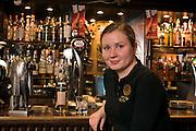 Yekaterinburg, Russia, 03/04/2006..Gordon's Scottish Music Pub waitress Anastasia Fyodorova with statuette of Lenin in Scottish hat.