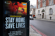 As the UK government tells the nation to prepare for the worst two weeks of the Coronavirus pandemic, a warning aimed at the population to stay at home and minimise contact with others, but in the week when new vaccination centres are opening, a 'Stay At Home' message is displayed at a bus shelter in Shoreditch, on 11th January 2021, in London, England.