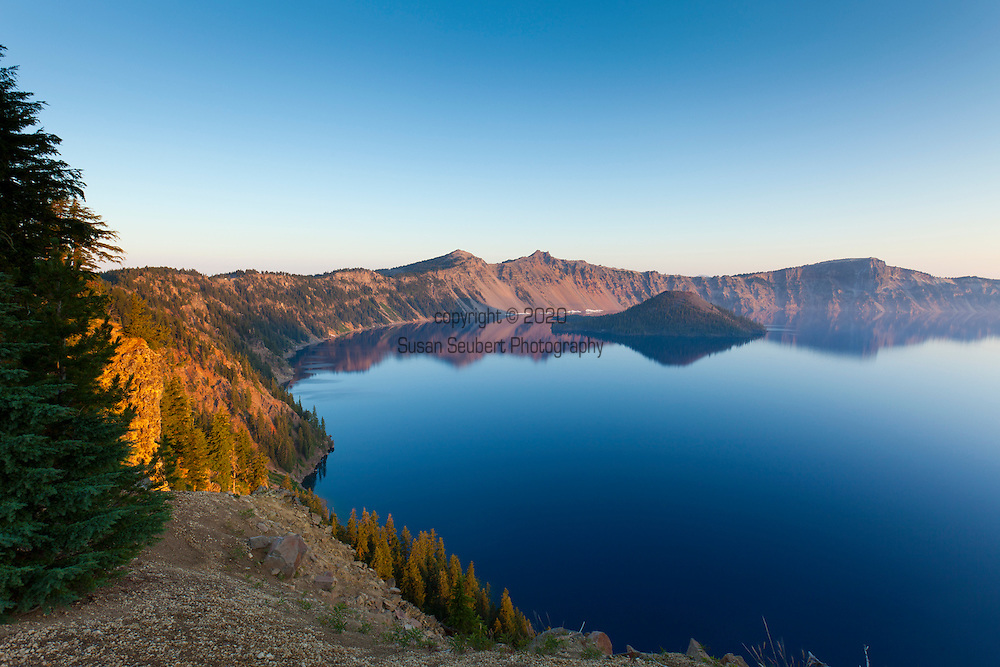 Crater Lake National Park, the only National Park in the state of Oregon, attracts some 482,000 people annualy. The lake itself is 592 meters (1,943ft) deep and is the deepest lake in the United States.  The park was founded in 1902 and seeks to preserve the natural and cultural resources.  Crater Lake lies in a caldera, or volcanic basin, created when Mt. Mazama collapsed around 7,700 years ago.  The clarity and blueness of the water are unique to this geologic area.  The lake is filled almost entirely by melted snow.  The lake is only accessibly by one trail, the Cleetwood Cove Trail, which leads down to the water for access to the tourist boats.  Crater Lake at sunrise.