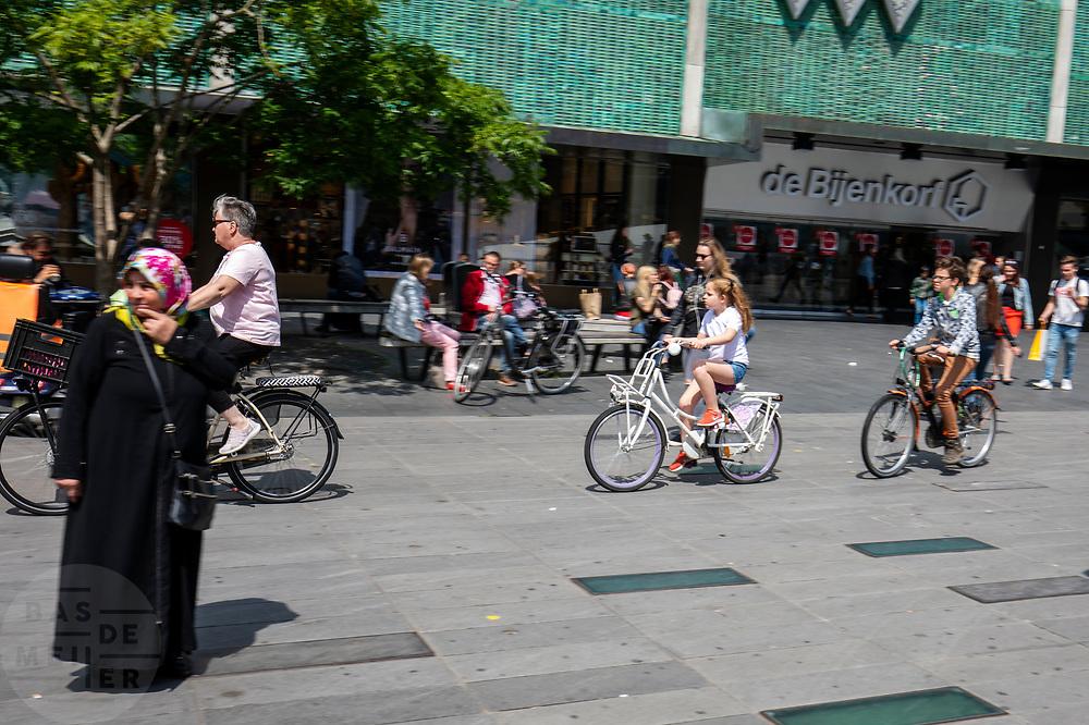 In Eindhoven rijdt een vrouw met kinderen achter haar aan op de fiets over het 18 septemberplein bij de Bijenkorf.<br /> <br /> In Eindhoven an woman cycles with children at the the city center.
