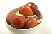 Gulab Jamun, an Indian dessert, drizzled with a sugar syrup.