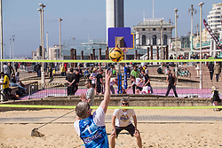 """© Licensed to London News Pictures.29/03/2021. Brighton,UK. Members of the public enjoy playing volleyball during spring weather in Brighton, East Sussex. From today (Monday), the """"Stay at Home"""" advice ends with people being allowed to meet up within the 'rule of six' and play group sports. Photo credit: Marcin Nowak/LNP"""