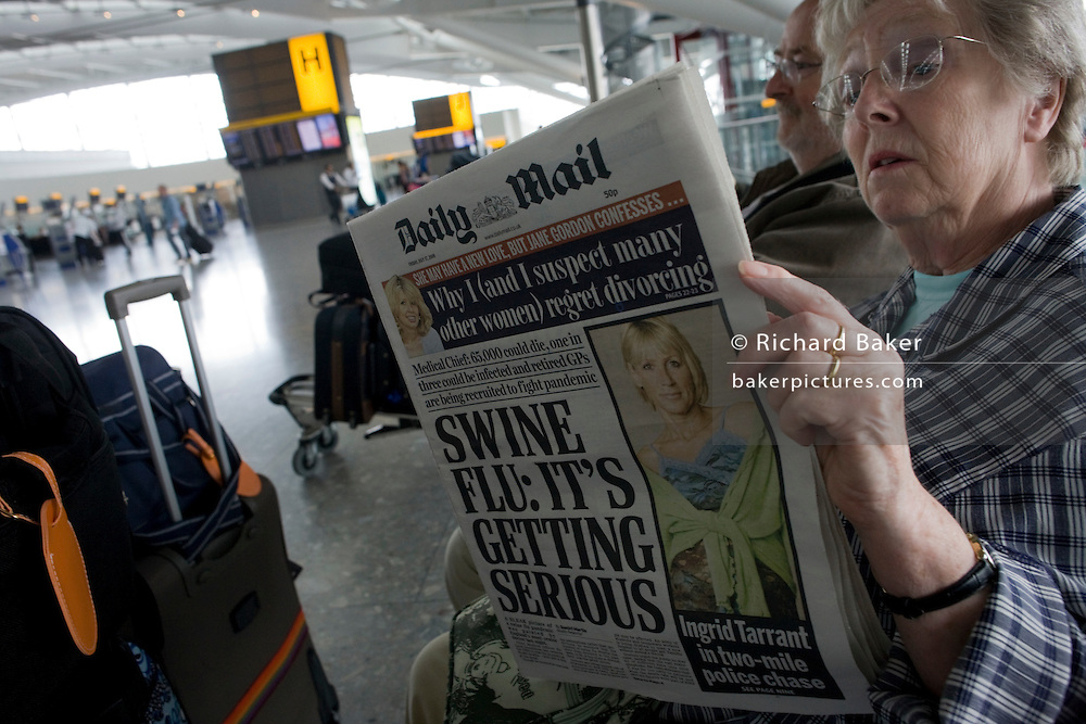 "Two elderly but travel-wise passengers read the morning newspapers while awaiting their check-in zone to open in Heathrow Airport's Terminal 5 departures concourse. The front page of the Daily Mail proclaims that Swine Flu is getting more serious after a period of summer when schools are about to re-open and temperatures about to drop for autumn. With their baggage stacked on a trolley the couple wait patiently after an early morning coach brought them to this aviation hub for BA only flights. From writer Alain de Botton's book project ""A Week at the Airport: A Heathrow Diary"" (2009). .."