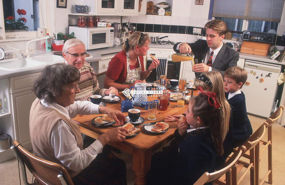 Family group with three generations eating breakfast at kitchen table,