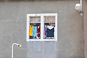 A window with clothes lines washing hanging to dry. White window frames, gray wall, colourful clothes. In Kamenari . Montenegro, Balkan, Europe.