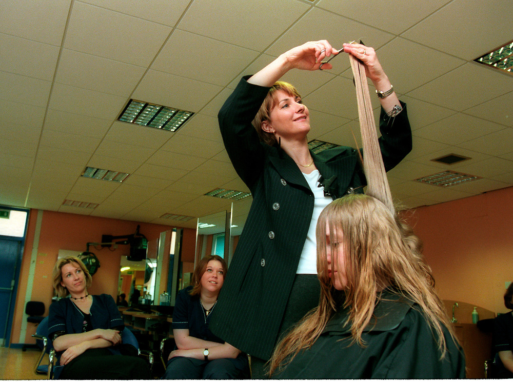 Further education  tutor demonstrating hair cutting and styling;