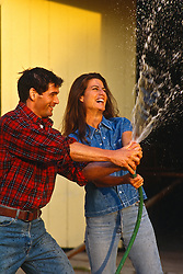 couple outside playing with a watering hose