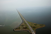 Nederland, Noord-Holland, Gemeente Wieringen, 28-04-2010; Den Oever, begin Afsluitdijk, gezien naar het noordoosten. De dijk vormt de waterkering tussen Waddenzee (li) en IJsselmeer (rechts). In de dijk de Stevinsluizen, spuisluizen of uitwaterende sluizen, het 'eiland' heet Robbenplaat. Aanleg van de dijk vormde onderdeel Zuiderzeewerken, initiatief van ingenieur Cornelis Lely..Den Oever, beginning Enclosure Dam, looking east. The dike forms the barrier between the Wadden Sea (li) and IJsselmeer lake (right). The Stevin sluices sluice surplus water to the Wadden sea. Construction of the dam was part of the Zuiderzee Works, an initiative of engineer Cornelis Lely..luchtfoto (toeslag), aerial photo (additional fee required).foto/photo Siebe Swart