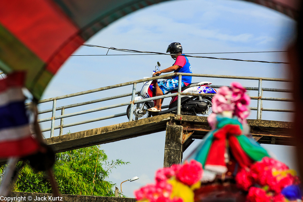 "17 NOVEMBER 2012 - BANGKOK, THAILAND:  A motorcyclist crosses bridge over a khlong or canal in the Thonburi section of Bangkok. Bangkok used to be known as the ""Venice of the East"" because of the number of waterways the criss crossed the city. Now most of the waterways have been filled in but boats and ships still play an important role in daily life in Bangkok. Thousands of people commute to work daily on the Chao Phraya Express Boats and fast boats that ply Khlong Saen Saeb or use boats to get around on the canals on the Thonburi side of the river. Boats are used to haul commodities through the city to deep water ports for export.    PHOTO BY JACK KURTZ"