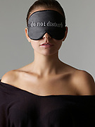 "Head shot of woman with sleeping mask that says ""Do Not Disturb"""