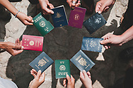 Travelers from around the world hold their passports in a circle at the monastery of Deir Mar Musa in Syria. Deir Mar Musa was established in the 6th century and dedicated to Saint Moses the Abyssinian.