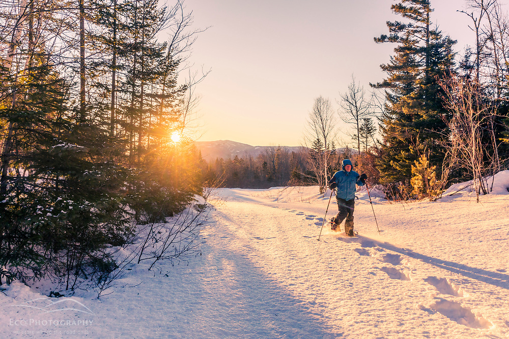 """A man snowshoes as the sun sets behind """"the Traveller"""" mountain as seen from a trail near Bowlin Camps, just outside of Katahdin Woods and Waters National Monument."""