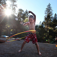A boy named Austin revels in the simplicity of carefree moment with a Hula Hoop at Camp Erin Santa Cruz at held at Ponderosa Lodge on Graham Hill Road. Camp Erin, created and supported by the Moyer Foundation, is the largest national bereavement program for youth grieving the death of a significant person in their lives. Children and teens ages 6-17 are provided a camp that combines traditional, fun camp activities with grief education and emotional support, free of charge for all families. .Camp Erin Santa Cruz  is a weekend-long camp for children and teens in Santa Cruz County, the greater Monterey Bay, Silicon Valley, and other areas. <br /> Photo by Shmuel Thaler <br /> shmuel_thaler@yahoo.com www.shmuelthaler.com