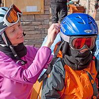 A mother adjusts her son's goggles at Big Sky ski area, Big Sky, Montana.