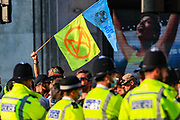 A demonstrator holds up a flag towards the Police officers during the group's 'Impossible Rebellion' series of actions at Oxford Circus in central London, on Wednesday, August 25, 2021. - Climate change demonstrators from environmental activist group Extinction Rebellion continued with their latest round of protests in central London, promising two weeks of disruption. (VX Photo/ Vudi Xhymshiti)