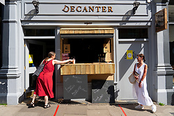 Edinburgh, Scotland, UK. 29 May 2020. Several bars and bistros are offering drinks to takeaway from their premises in Edinburgh. Customers outside Decanter bistro in Bruntsfield which has built a small counter to serve drinks to the street. Iain Masterton/Alamy Live News