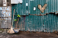 A broom and potted plant lean against green corrugated metal sheets on which a heart is painted, Tay Ho District, Hanoi, Vietnam, Southeast Asia