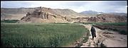 A man walks towards an ancient ruin in Bamiyan Valley.