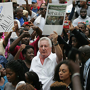 """A George Zimmerman supporter (white shirt) stirs up the crowd as protesters march and hold signs in the No Justice No Peace- """"March Against Gun Violence""""  walk from Lake Eola in downtown Orlando, to the Orange County Courthouse on Wednesday, July 17, 2013. The march was organized by the Modarres Law Firm and Orlando attorney Natalie Jackson, one of the attorneys for Trayvon Martins parents. (AP Photo/Alex Menendez)"""