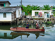 """22 MARCH 2018 - BANGKOK, THAILAND: A boat goes past a demolished home on the bank of Khlong Lat Phrao. Bangkok officials are evicting about 1,000 families who have set up homes along Khlong  Lat Phrao in Bangkok, the city says they are """"encroaching"""" on the khlong. Although some of the families have been living along the khlong (Thai for """"canal"""") for generations, they don't have title to the property, and the city considers them squatters. The city says the residents are being evicted so the city can build new embankments to control flooding. Most of the residents have agreed to leave, but negotiations over compensation are continuing for residents who can't afford to move.      PHOTO BY JACK KURTZ"""