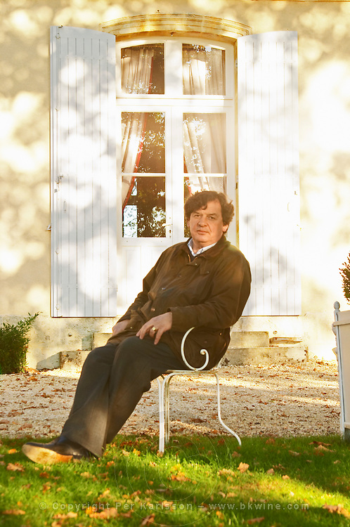 Comte (count) Laurent de Bosredon, owner of Chateau Belingard sitting in front of his chateau in a garden chair in autumn evening sunshine Chateau Belingard Bergerac Dordogne France