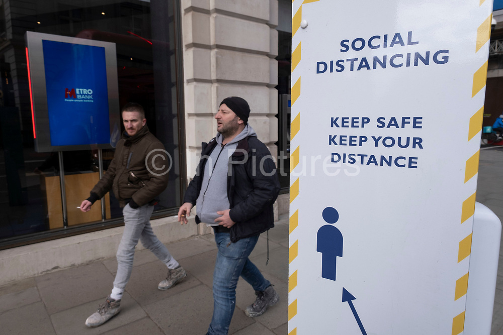Social distancing sign on Piccadilly as the national coronavirus lockdown three continues on 5th March 2021 in London, United Kingdom. With the roadmap for coming out of the lockdown has been laid out, this nationwide lockdown continues to advise all citizens to follow the message to stay at home, protect the NHS and save lives, and the streets of the capital are quiet and empty of normal numbers of people.