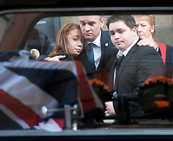 © London News Pictures. 10/03/2012.  Newcastle, UK. L to R Mia Rathband (Daughter) Darren Rathband (Brother) and Ashley Rathband (Son) watch the coffin leaving Newcastle Cathedral in Newcastle upon Tyne  following  a formal police memorial service in the memory of PC David Rathband, who was found dead in his Northumberland Home on February 29. PC David Rathband was left blind after being shot in the face by gunman Raoul Moat.  Photo credit : Ben Cawthra/LNP