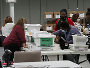 Absentee mail-in ballots are sorted into precincts after the signatures and registrations are verified.