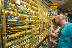Tourists looking at window display of ornate gold jewellery shop at the Gold Souk in Deira Dubai United Arab Emirates