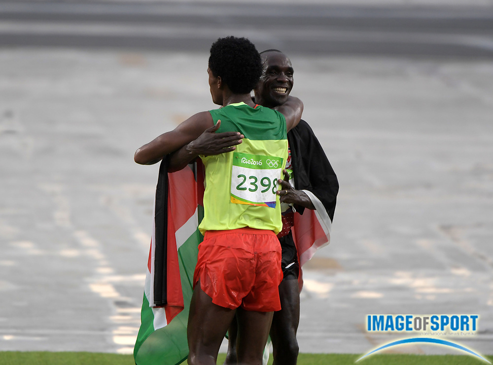 Aug 21, 2016; Rio de Janeiro, Brazil; Eliud Kipchoge (KEN), left, and Feyisa Lilesa (ETH) embrace after placing first and second in the marathon during the Rio 2016 Summer Olympic Games at Sambodromo.