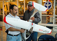 Garden City, New York, USA. 19th May 2013. DENNIS ANDREAS, at left, of Freeport, and RICHARD TIO, at right, of Brooklyn, are looking at a large ICON A5, a Horizon Hobbies kit made white and red model airplane, at the 8th Annual Flying Model Show sponsored by Academy of Model Aeronautics (AMA) and Model Airplane Clubs of Nassau, Suffolk & Queens, in the lobby of the Cradle of Aviation Museum.